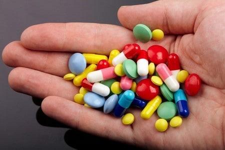 Таблетки и капсулы в руке