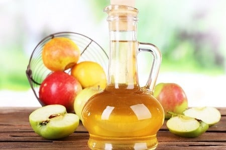 Бутылка яблочного уксуса и яблоки