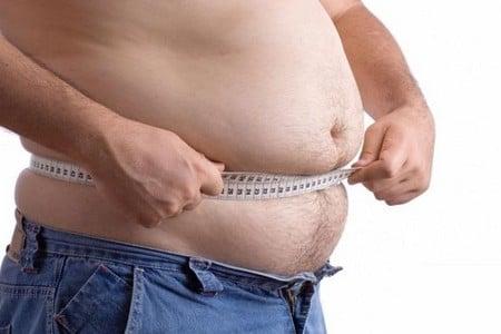 Мужчина измеряет свой живот