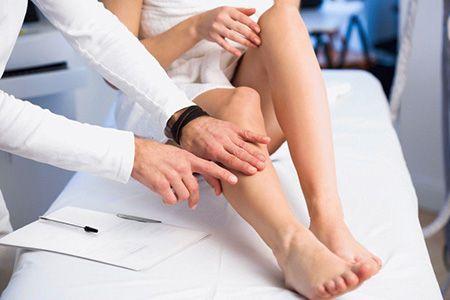 врач осматривает ноги пациентки