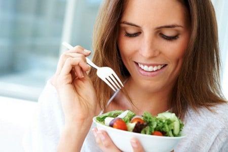 Женщина держит тарелку салата